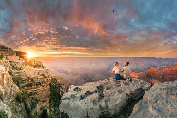 Man and woman sit on the edge of rim talking about future and watching the Grand Canyon sunset stock photo