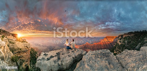 This is a panoramic photograph of a man and a woman sitting on the edge of rim, talking about future and watching the Grand Canyon sunset while bird in the sky