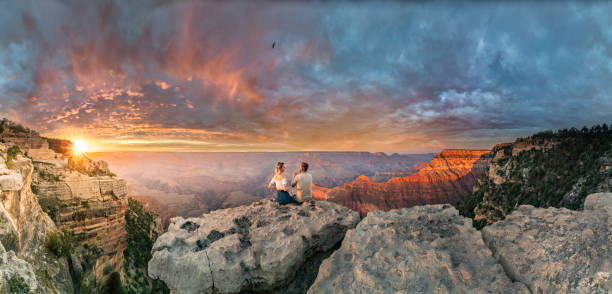 Man and woman sit on the edge of rim talking about future and watching the Grand Canyon sunset while bird in the sky stock photo