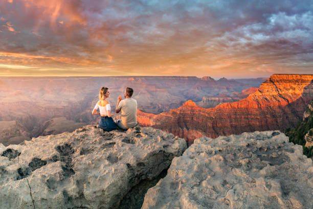 Man and woman sit on the edge of the rim having great conversation during the Grand Canyon sunset stock photo