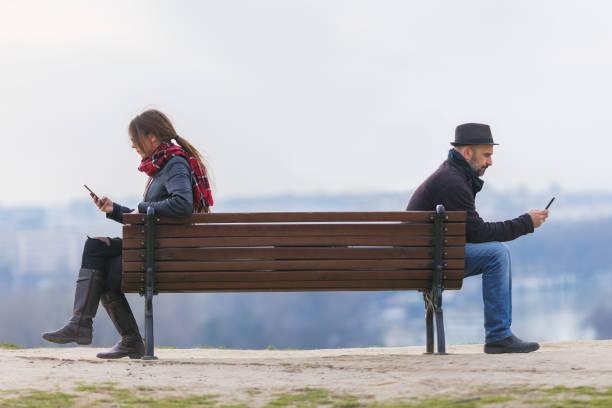hombre y mujer sentados separados en un banco - foto de stock