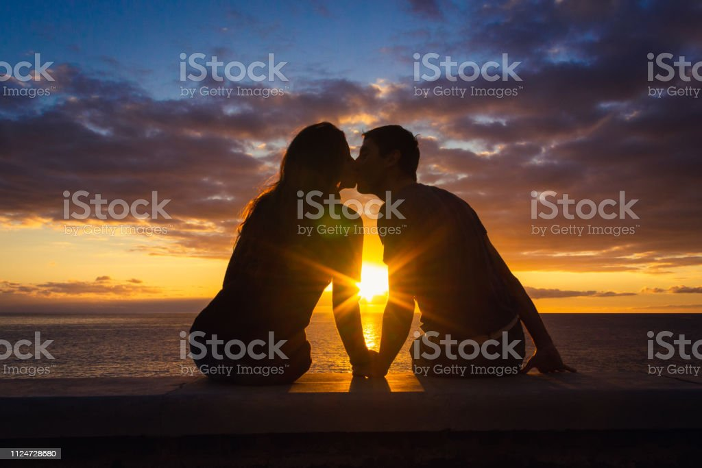 Man and woman sitting by the sea kissing at sunset at Meloneras beach walk, Gran Canaria Couple silhouette enjoying romantic colorful twilight. Valentines Day, honeymoon romantic date concepts Adult Stock Photo