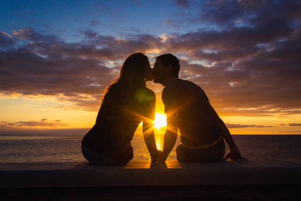 Man and woman sitting by the sea kissing at sunset at Meloneras beach walk, Gran Canaria Couple silhouette enjoying romantic colorful twilight. Valentines Day, honeymoon romantic date concepts passion stock pictures, royalty-free photos & images