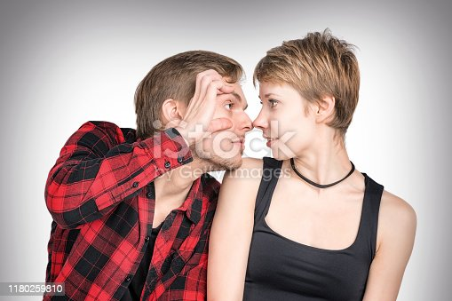 Man and woman sitting close together looking at each other. Man and woman looking at each other. On gray background