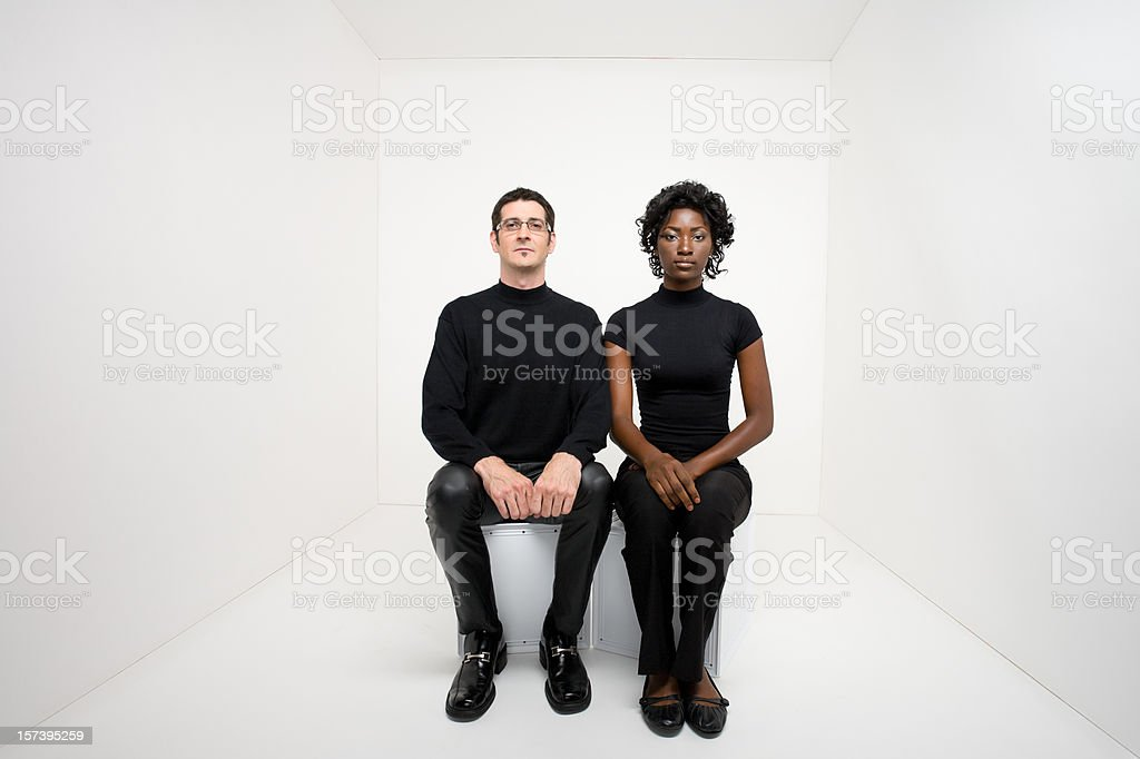 Man and woman sitting in a white room facing camera stock photo