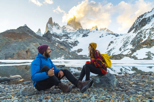 Man and woman sitting near the lake on the background of Fitz Roy mountain in Patagonia stock photo