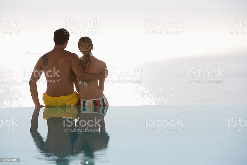 Man and woman sitting on edge of swimming pool stock photo