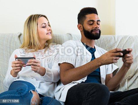 istock man and woman sitting on sofa 531711056