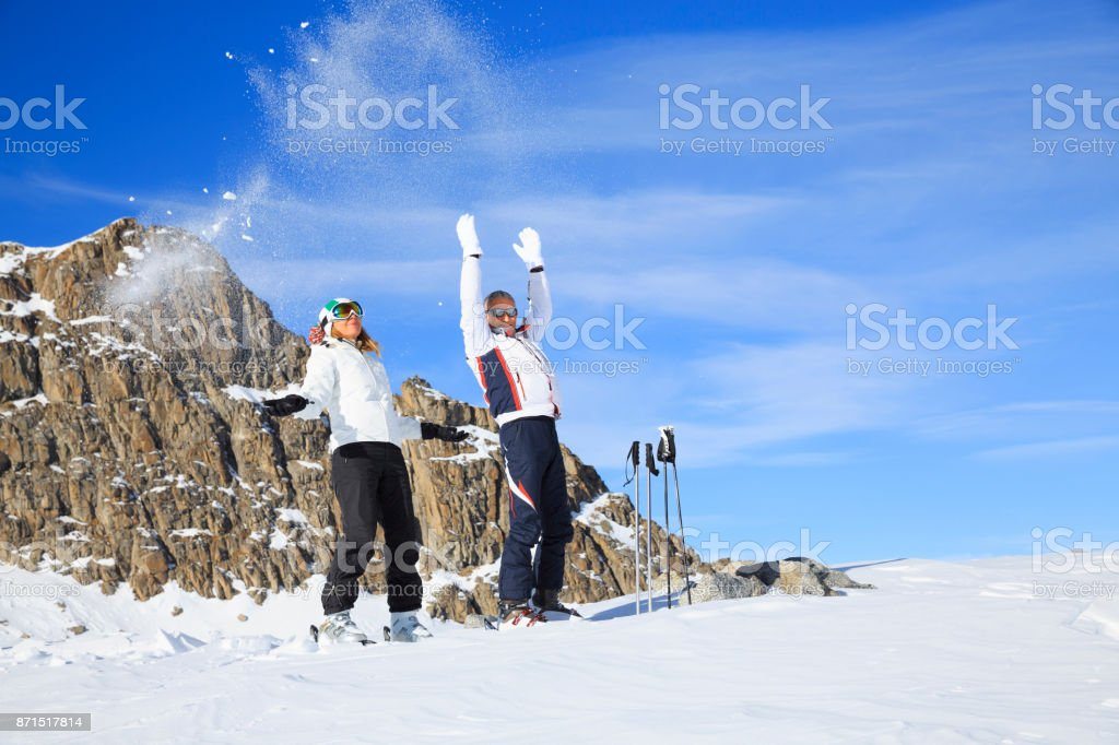 Man and woman skiers play with the snow at ski resort Dolomites in Italy stock photo