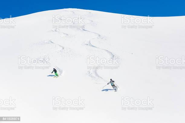 Man and woman skiing down mountain picture id841505974?b=1&k=6&m=841505974&s=612x612&h=tmigh5iagzn8oirudr7m3 ftmwxkx0a4 orxn jlcl8=