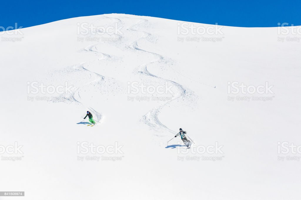 Man and woman skiing down mountain stock photo