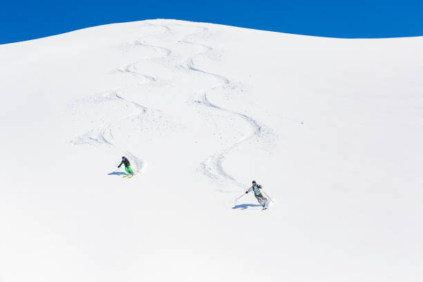 Man and woman skiing down mountain Man and woman skiing down mountain leaving tracks behind new territories stock pictures, royalty-free photos & images