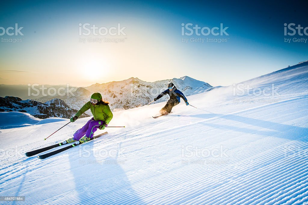 Man and woman skiing downhill stock photo