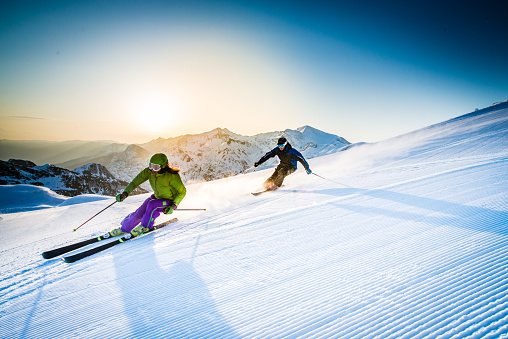 Man And Woman Skiing Downhill Stock Photo - Download Image Now