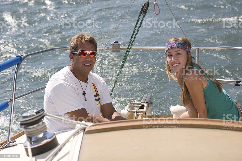 Man and Woman Smiling while Sailing on Sail Boat royalty-free stock photo