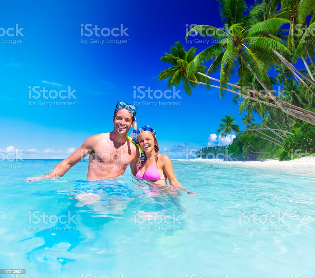A man and woman smiling while snorkeling in a clear blue sea royalty-free stock photo