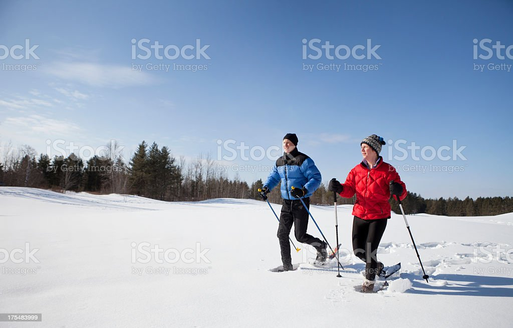 Man and Woman Snowshoeing on a Sunny Winter Day. stock photo