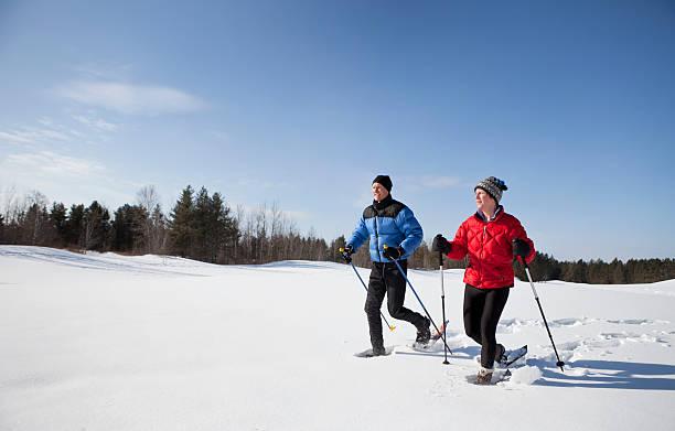 homme et femme de la marche en raquettes sur une belle journée d'hiver. - raquette photos et images de collection
