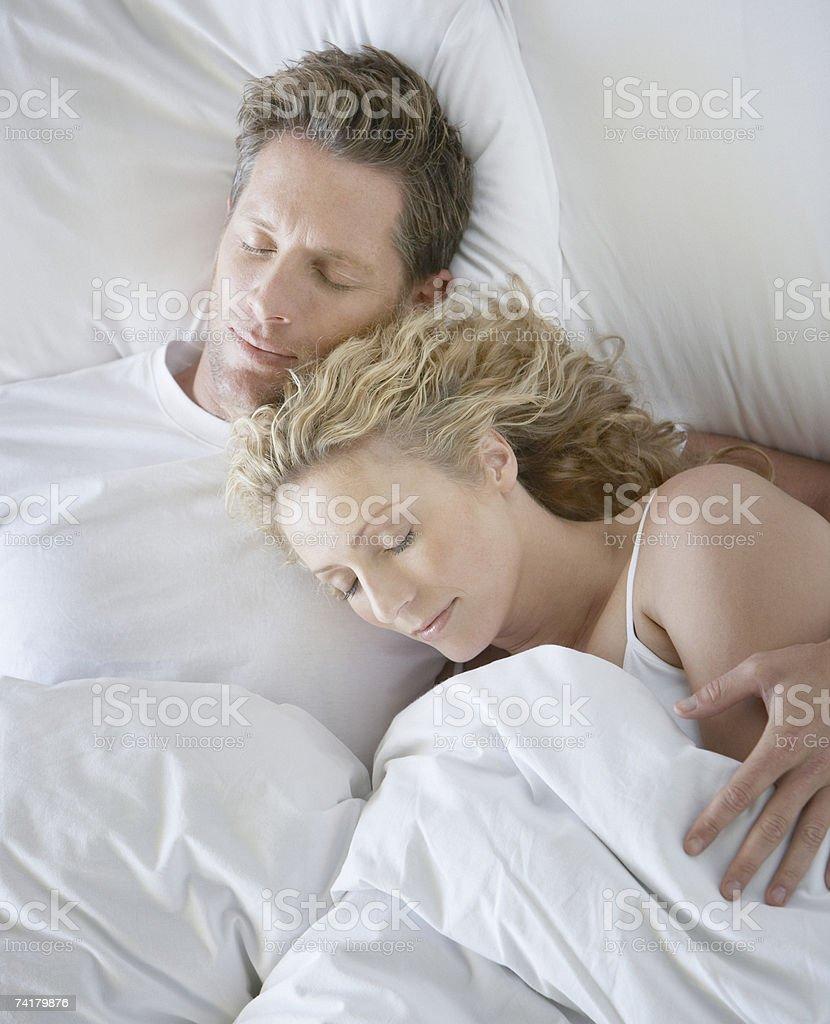 Homem e mulher na cama a dormir snuggling foto de stock royalty-free