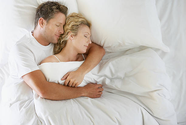 Man and woman snuggling in bed asleep stock photo