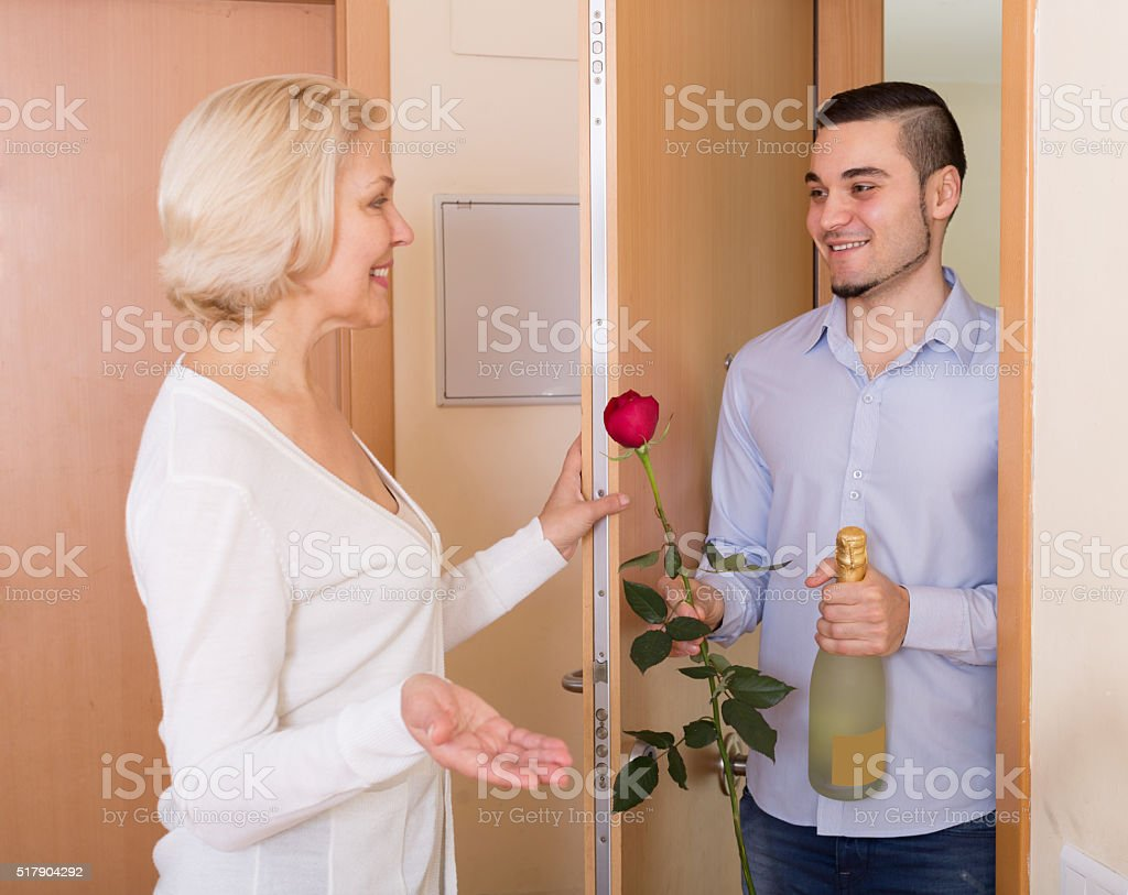 man and woman standing at doorway stock photo