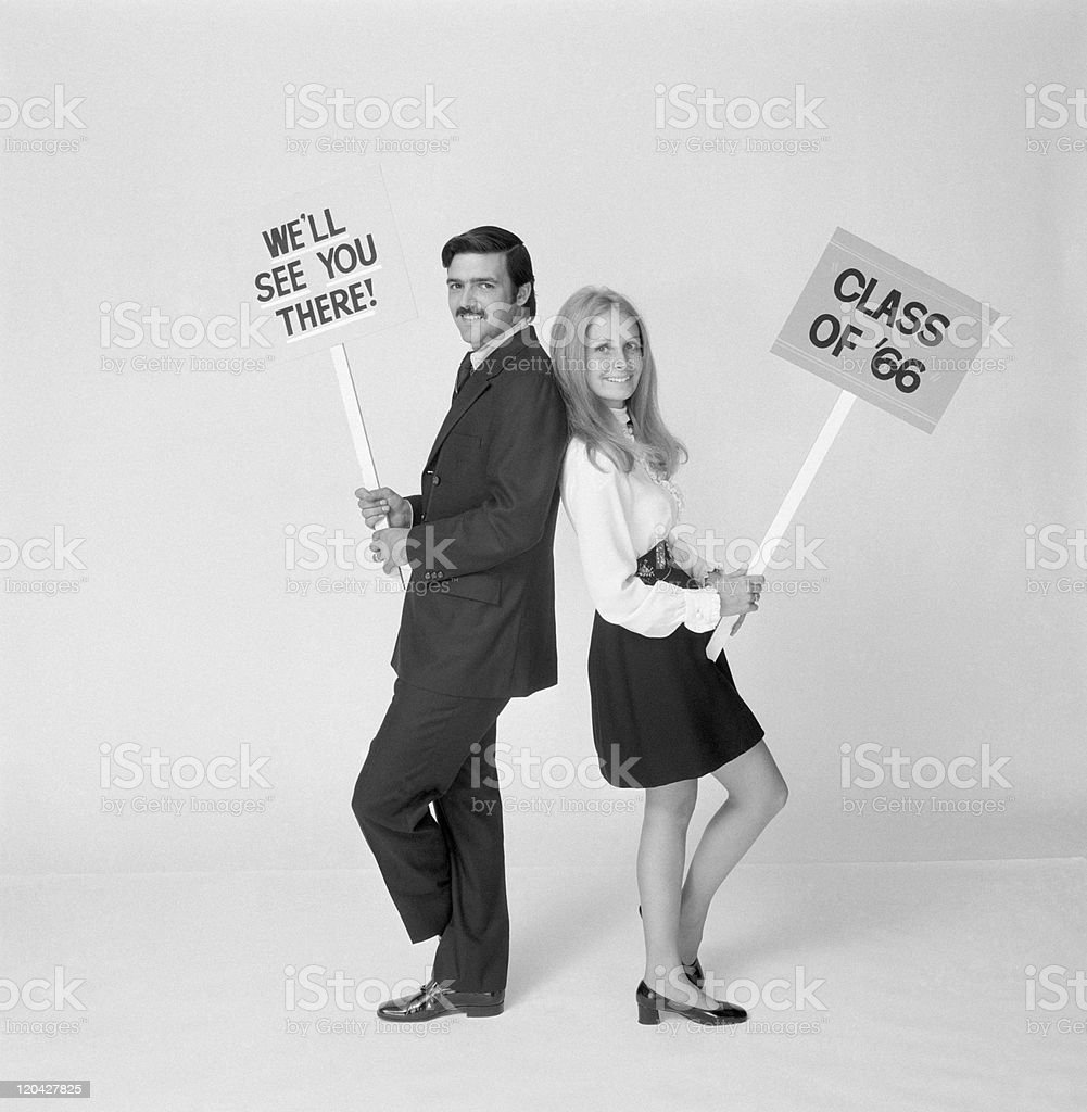 Man and woman standing back to back holding placards, smiling, portrait stock photo
