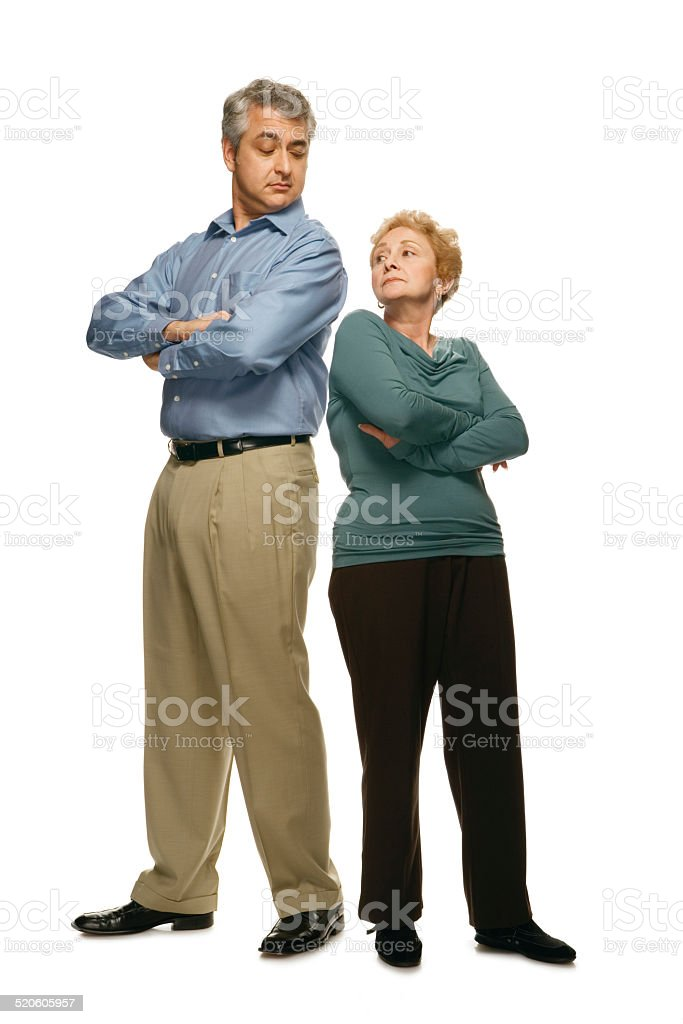 Man and woman standing back to back with arms crossed stock photo