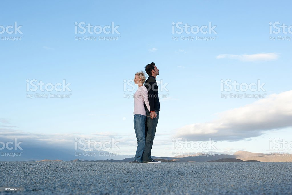 Man and woman standing back-to-back stock photo