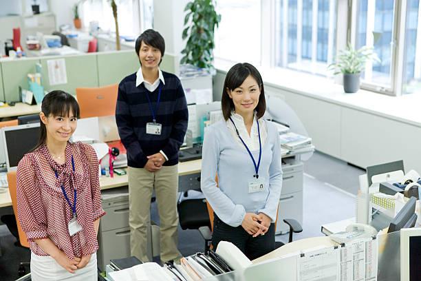 Hombre y mujer de pie por escritorio - foto de stock