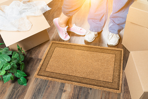 istock Man and Woman Standing Near Blank Welcome Mat, Moving Boxes and Plant 1060295998