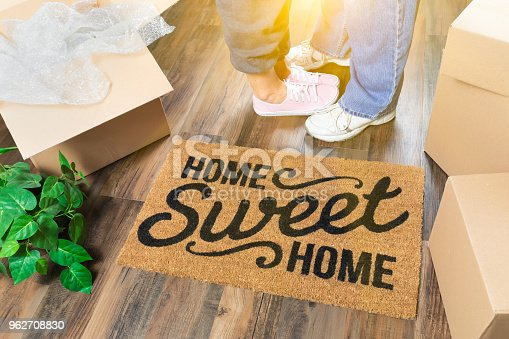 istock Man and Woman Standing Near Home Sweet Home Welcome Mat, Moving Boxes and Plant 962708830