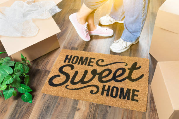 man and woman standing near home sweet home welcome mat, moving boxes and plant - home sweet home imagens e fotografias de stock