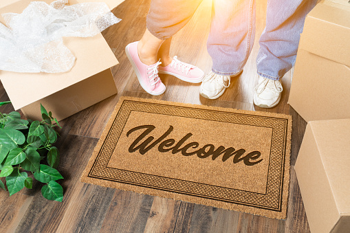 istock Man and Woman Standing Near Welcome Mat, Moving Boxes and Plant 1060557802