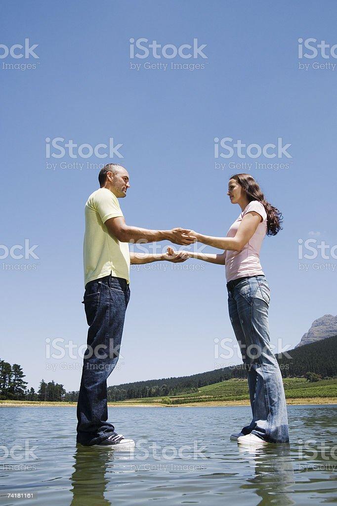 Homem e mulher em pé na água de mãos dadas foto de stock royalty-free