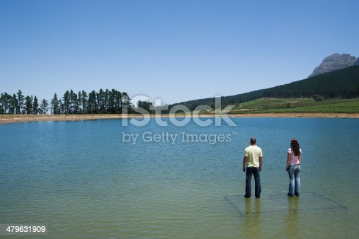 istock Man and woman standing on water  479631909