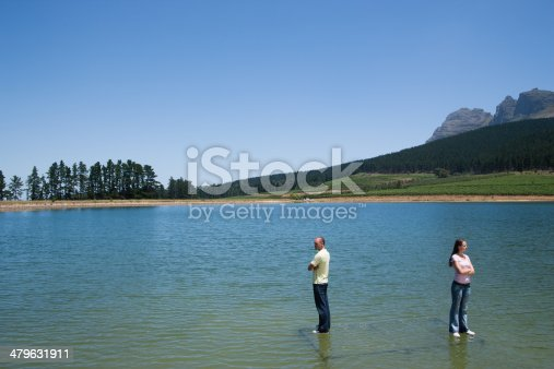 istock Man and woman standing on water with arms crossed back to back 479631911