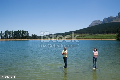istock Man and woman standing on water with arms crossed back to back 479631913