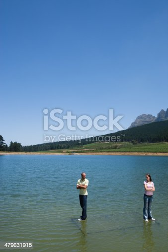 istock Man and woman standing on water with arms crossed back to back 479631915