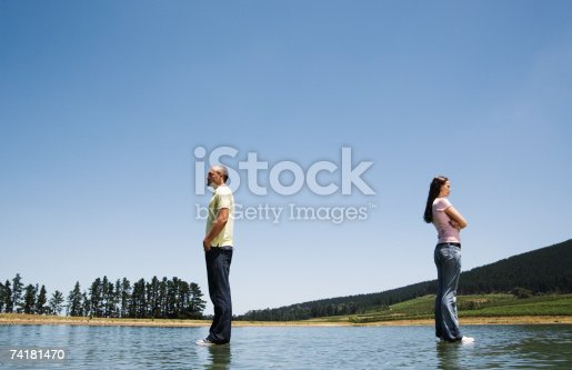 istock Man and woman standing on water with arms crossed back to back 74181470