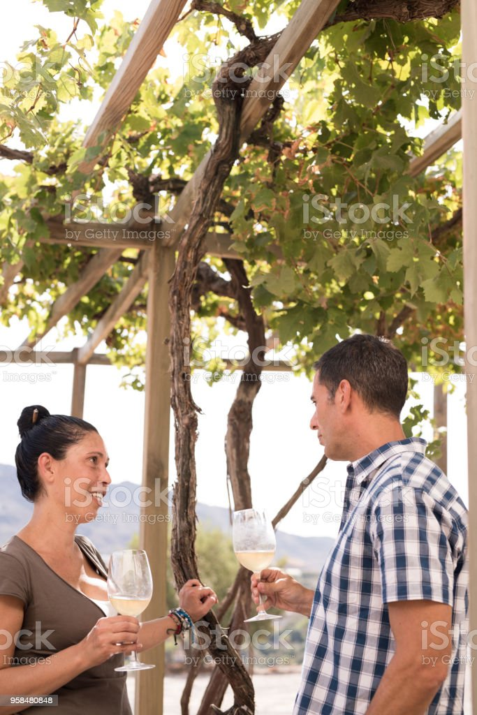A man and woman standing under a vine canopy stock photo