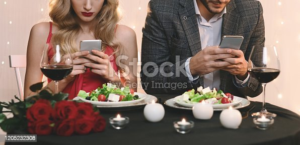 istock Man And Woman Stuck In Their Smartphones On Date In Restaurant 1205232308