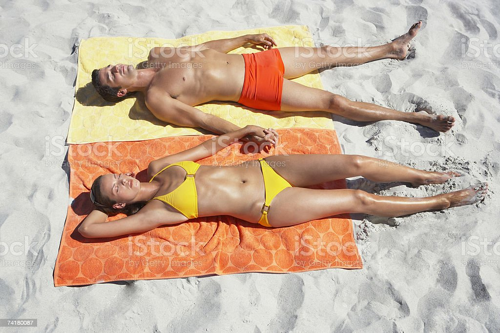 Man and woman sunbathing on beach towels in sand royalty-free stock photo