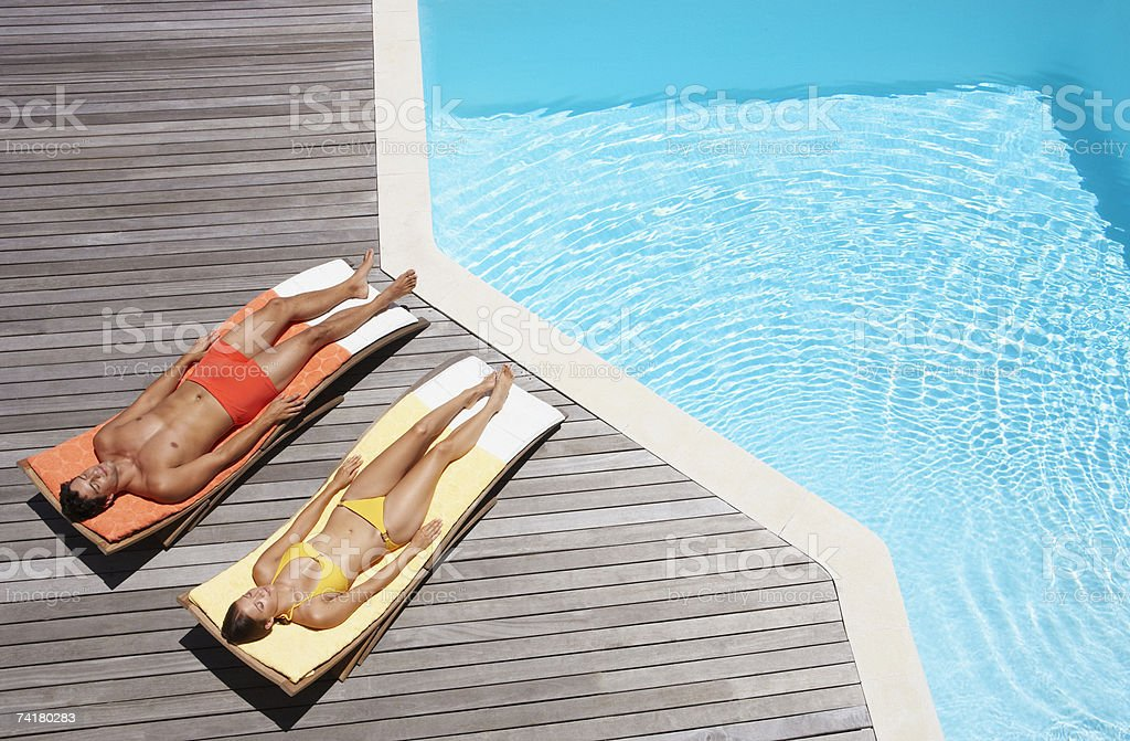 Homme et femme prenant un bain de soleil sur la terrasse de la piscine - Photo