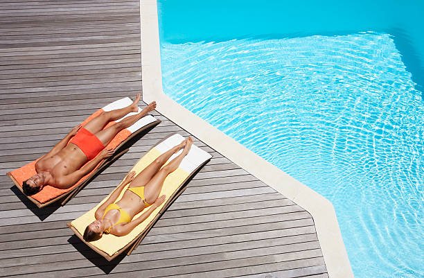 Man and woman sunbathing on pool deck  sunbathing stock pictures, royalty-free photos & images