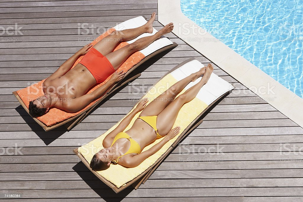 Man and woman sunbathing on pool deck royalty-free stock photo