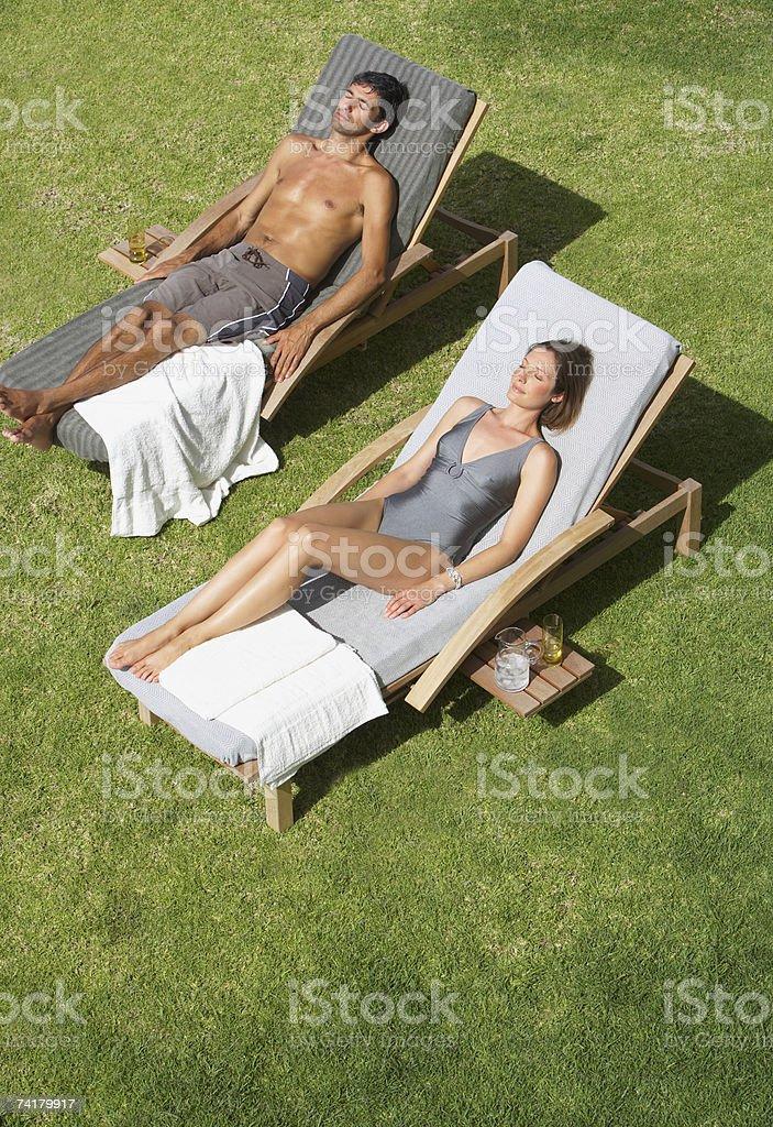 Homem e mulher a apanhar sol ao ar livre foto de stock royalty-free