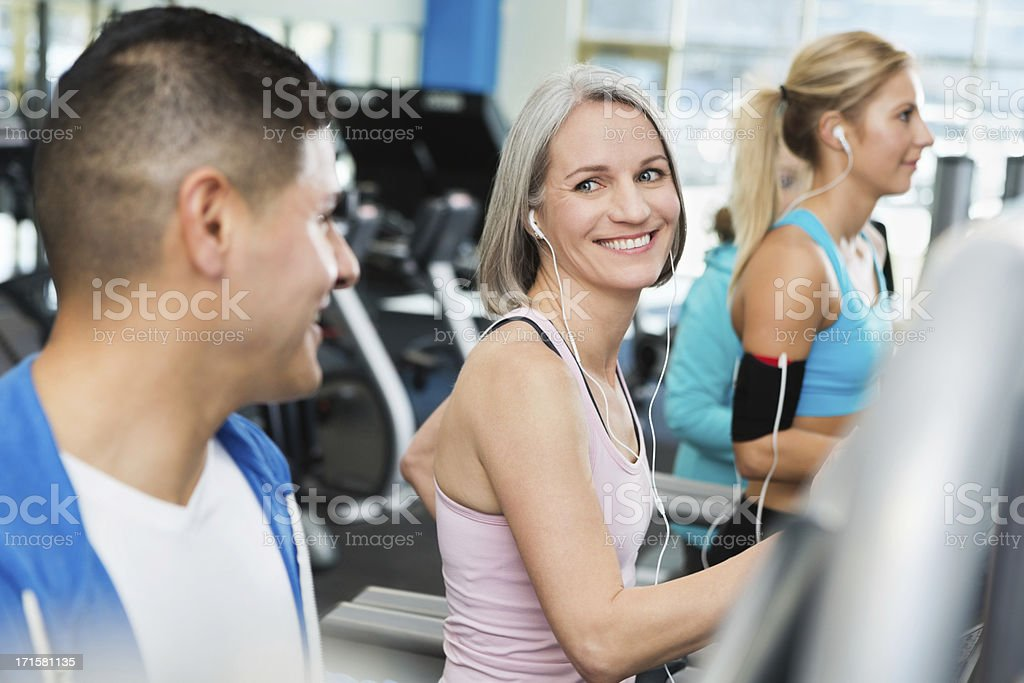 Man and woman talking in gym on treadmills while exercising royalty-free stock photo