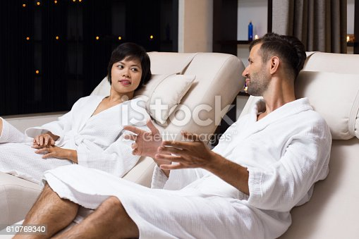 istock Man and Woman Talking on Loungers in Spa Salon 610769340