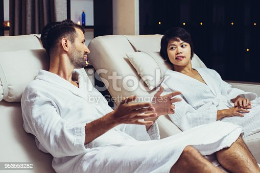 610769340istockphoto Man and Woman Talking on Loungers in Spa Salon 953553282