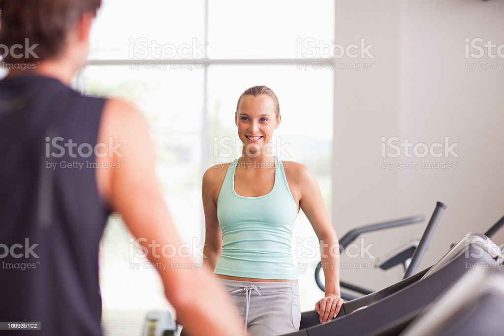 Man and woman talking on treadmills in gymnasium royalty-free stock photo